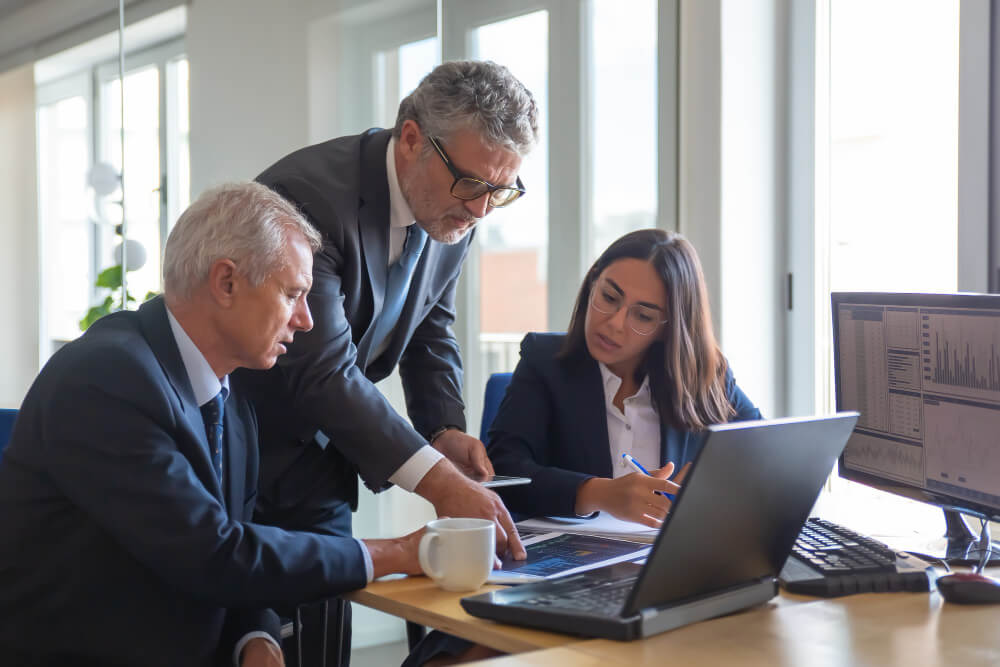 concentrated-colleagues-watching-statistic-charts-talking-about-work-professional-senior-managers-young-assistant-preparing-business-plan-teamwork-management-partnership-concept (1)